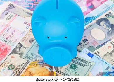 Blue piggy bank on international banknote background