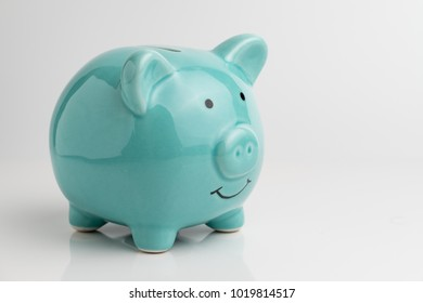 Blue piggy bank on reflection floor and seamless white background.