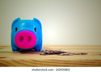 Blue piggy bank on wooden table over wall grunge background