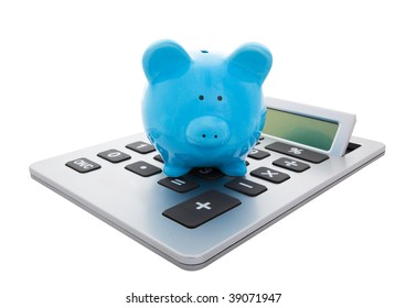 A blue piggy bank sitting on a large calculator.  Conceptual savings.  Isolated with clipping path.