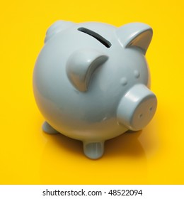 Blue piggy bank style money box on a yellow studio background.