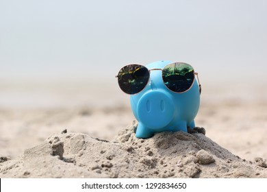 Blue piggy bank with sunglasses on sea beach, Saving planning for Travel budget of holiday concept