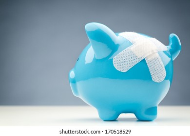A blue piggy bank with a white bandage standing on a white surface with copy space in the background.