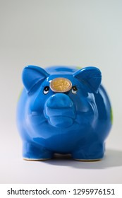 Blue piggybank with a two euro coin balanced on the nose