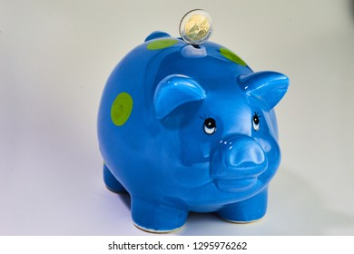 Blue piggybank with a two euro coin balanced on the back