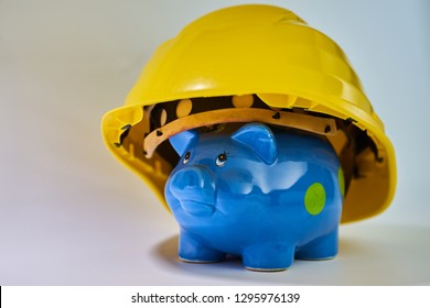 Blue piggybank with yellow construction helmet isolated on white background