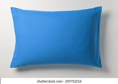 Blaues Kissen auf weißem Hintergrund mit echtem Schatten. Draufsicht eines weichen bunten Kissen mit Kopienraum für Tex oder Bild