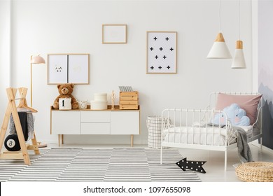 Blue pillow on white bed in scandi kid's bedroom interior with mockup of empty poster