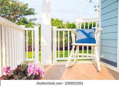 A blue pillow on a wooden white rocking chair  in balcony by the blue wooden wall with nature background.