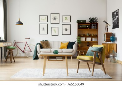 Blue pillow on yellow armchair next to wooden table on carpet in retro living room with sofa and bike