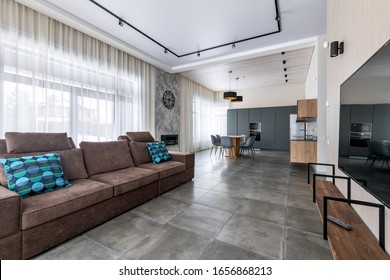 blue pillows, a large room in a country house, clean light interior. A bright space for a large family. Home theater. The kitchen is combined with the living room. Pure design.