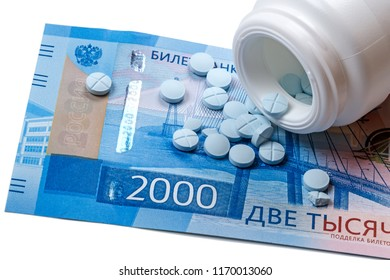 Blue pills and a 2000 rubles banknote on a white background