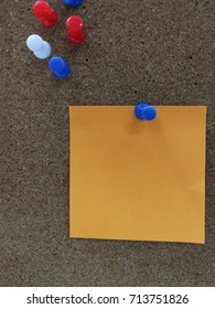 Blue pin fixing orange paper on the board. Many pins are available on the board. To present in a theme of business like making a short note or important for reminder or even put a nice message to peer