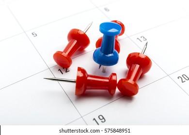 Blue pin on White Calendar Closeup shot.