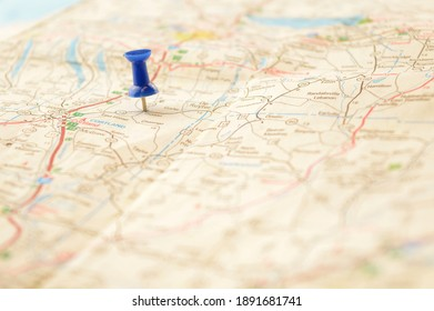 A blue pin pressed into a map detailing a point of interest.