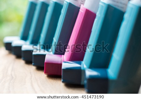 Blue and pink asthma inhalers in a line