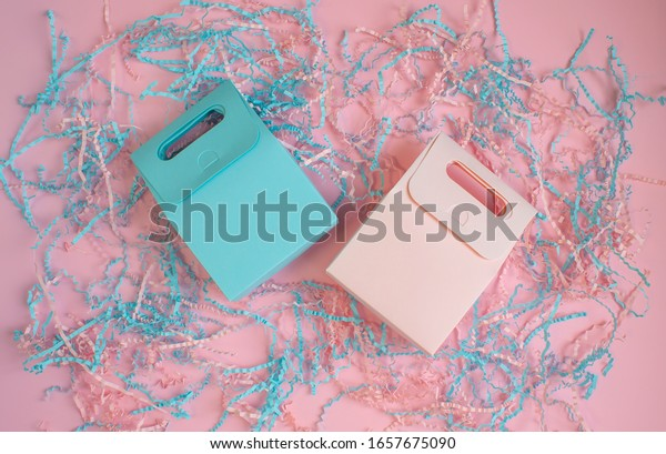 Blue and pink gift bags on pink background with shredded paper