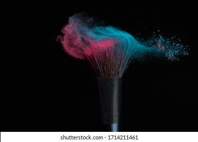 Maquillage bleu et rose sur une brosse à poudre frappée dans un nuage mixte