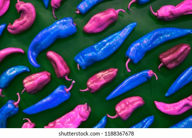 blue and pink peppers shapes creative pattern on a green background. Vegetables and food figures abstract colorful background. Top view. Pop art style. Creative composition.