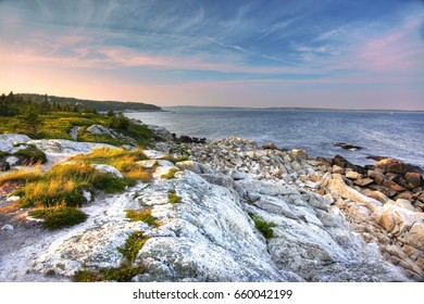 blue and pink sky over the ocean with white rocks