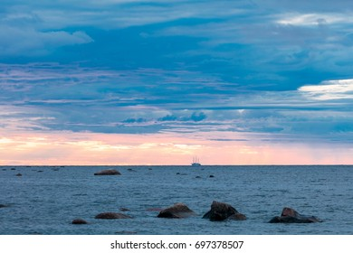 Blue and pink sunset sky above rocky beach and sail ship at summer Gulf of Finland, Russia