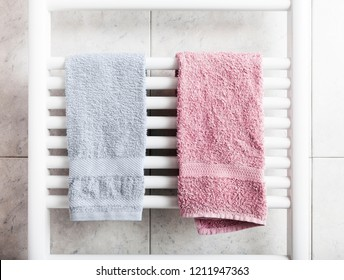 Blue and pink towels on a heater