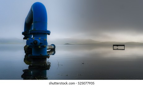 Blue pipe in a lake - Foggy morning in Spain