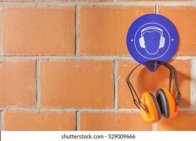 an blue placard for compulsory wearing of ear protection and a hearing protector on the hook