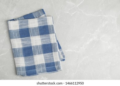 Blue plaid kitchen towel on light marble background, top view. Space for text