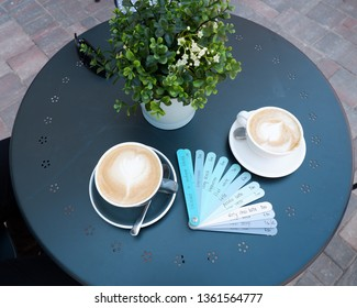blue planks menu with various drinks names and cup of coffee on blue table