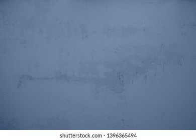 blue plastered concrete wall with heavily roughened structures in the center of the picture.