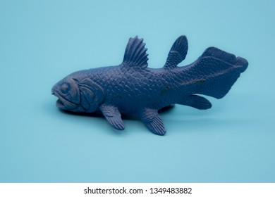Blue plastic Coelacanth toy on a blue background closeup with detail.