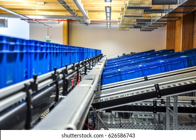 Blue plastic containers on roller conveyors in an automated high bay warehouse in Germany. The boxes are used in the logistics chain transporting the produced goods. Selective focus.