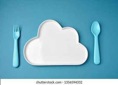 Blue plastic dishes and white plate on blue background. Concept