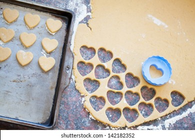 Blue plastic heart shaped cookie cutter and raw dough cookies on metal baking tray