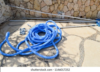 Blue plastic long large corrugated hose for cleaning the pool wash and watering the plants.
