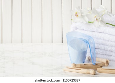 Blue plastic measuring beaker with detergent, stack of white terry towels, wooden clothespins and white orchid flower are on a marble surface against a white background of wooden planks