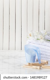 Blue plastic measuring beaker with detergent, stack of white terry towels, white orchid flower and wooden clothespins are on a marble surface against a white background of wooden planks