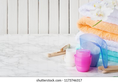 Blue plastic measuring vessel with washing powder, containers with detergent, stack of white terry towels, wooden clothespins and white orchid flower are on a marble surface