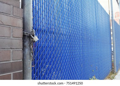 Blue plastic and metal security fence and gate secured with a heavy padlock