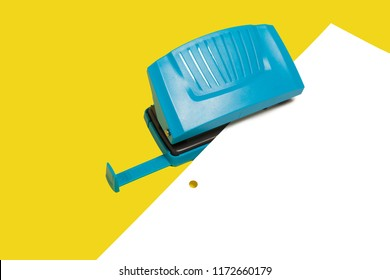 Blue plastic modern new office hole puncher lying with a paper isolated on a yellow background. free copyspace