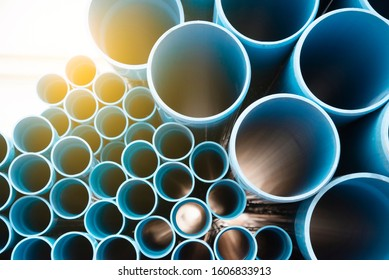 Blue plastic pipes used in construction site. Blue PVC water pipe in storage. Packaged blue plastic water pipes at warehouse.