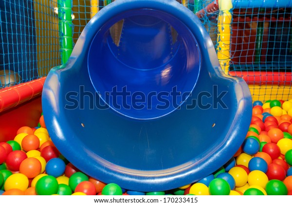 Blue plastic slide and pool covered with colourful balls in the kid's playground.
