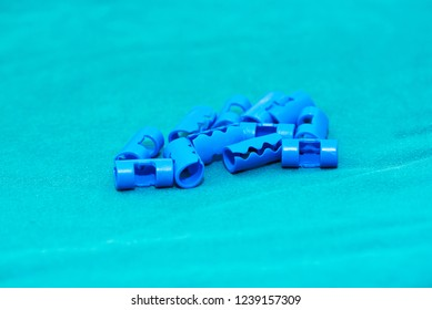 Blue plastic surgical clips for scalp hemostasis in brain surgery on green table in operating room