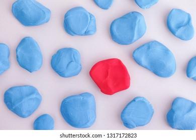 Blue plasticine pieces around a red one. Close up.