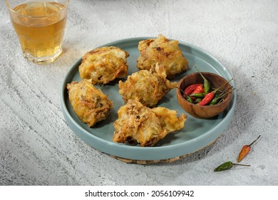A blue plate containing Bakwan Sayur or Bala Bala, a type of Indonesian traditional fritter snacks,  complete with cayenne pepper. Complementary drinking a glass of tea