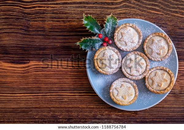 A blue plate with homemade, fresh British Mince Pies for Christmas on a wooden table