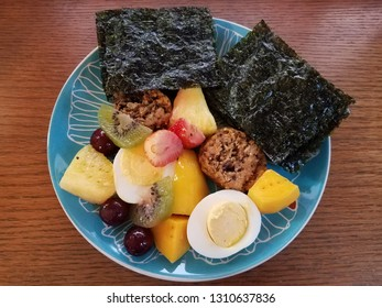 blue plate on wood surface with mango, egg, pineapple, and seaweed