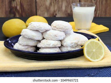 A blue plate stacked with sugared lemon cookies with lemons and milk.