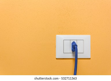 Blue Plug Inserted in a Wall Socket on an Orange Interior Wall